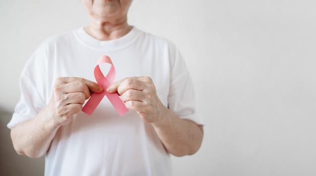 La mujer mayor apoya el día contra el cáncer de mama mediante la celebración de concienciación sobre el cáncer de mama con la cinta rosa.