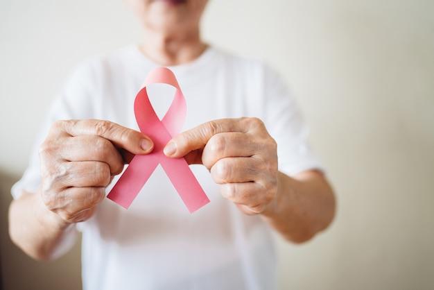 La mujer mayor apoya el día contra el cáncer de mama mediante la celebración de concienciación sobre el cáncer de mama con la cinta rosada.