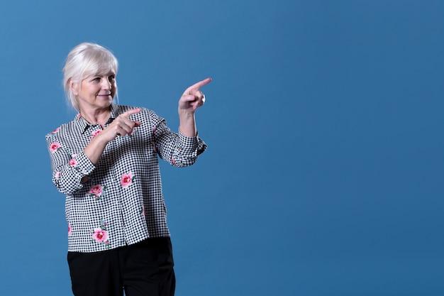 Mujer mayor apuntando hacia su izquierda