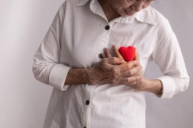 La mujer mayor asiática lleva a cabo la forma roja del corazón, concepto de enfermedad cardíaca.