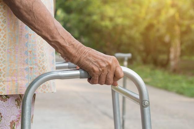 Mujer mayor asiática que se coloca con sus manos en un bastón