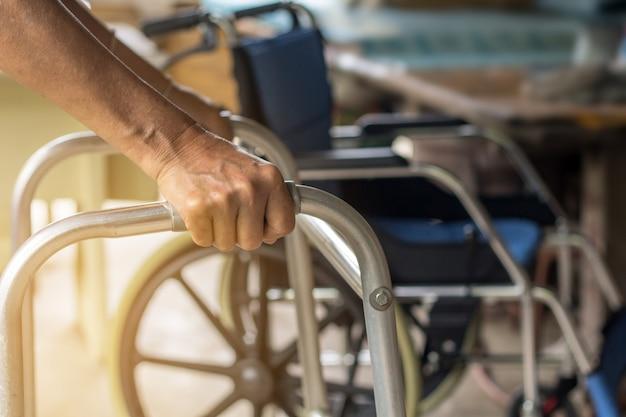 Mujer mayor asiática que se coloca con sus manos en un soporte del caminante