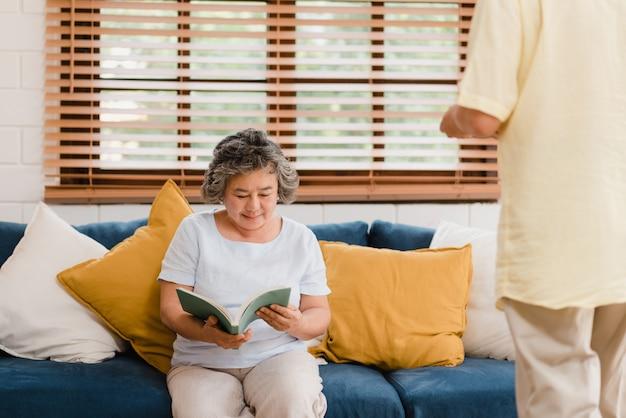 Mujer mayor asiática que lee un libro en sala de estar en casa. hembra china que miente en el sofá cuando está relajado en casa.