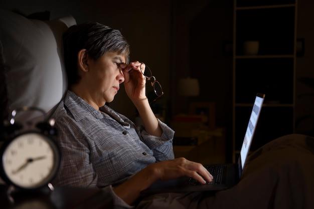 Mujer mayor asiática que tiene ojos doloridos y cansados cuando usa una computadora portátil en su cama por la noche