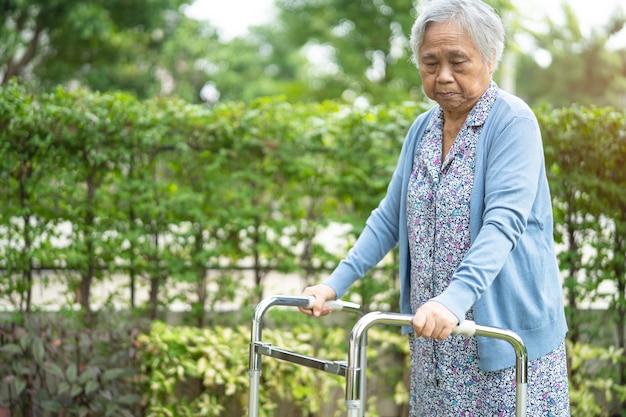 Mujer mayor asiática usa andador con fuerte salud mientras camina en el parque