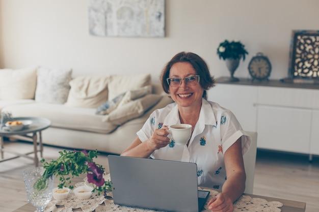 Mujer mayor bebiendo café y sonriendo en casa en camisa blanca durante el día