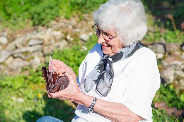 Mujer mayor buscando algo en su monedero