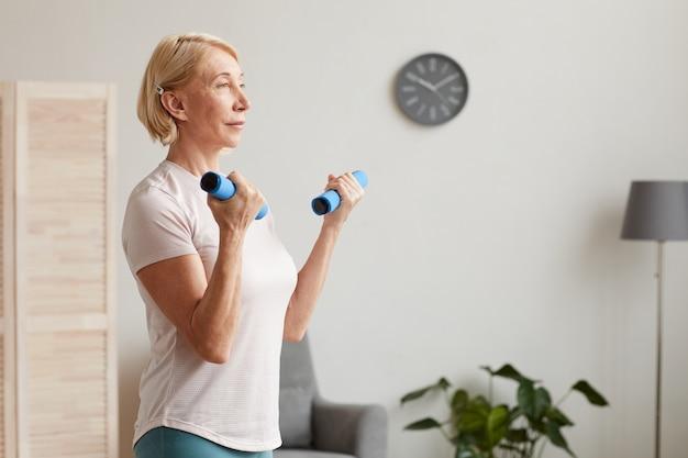 Mujer mayor con cabello corto rubio sosteniendo pesas en sus manos y haciendo ejercicio mientras está de pie en la habitación