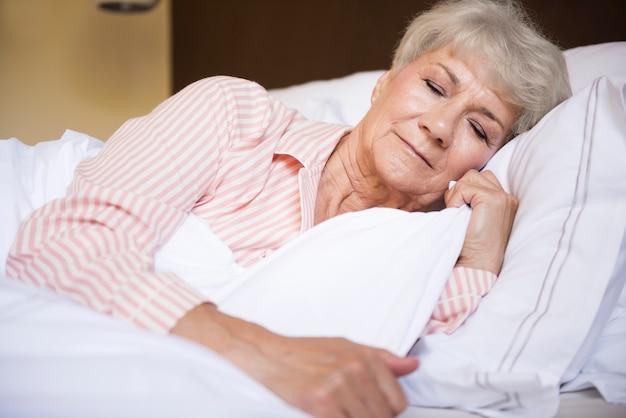 Mujer mayor cansada en la cama