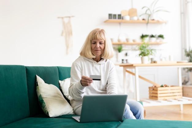 Mujer mayor en casa de compras en línea con computadora portátil y tarjeta de crédito