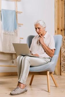 Mujer mayor contemplada que se sienta en la butaca que mira la computadora portátil