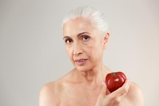 Mujer mayor desnuda concentrada que sostiene la manzana.