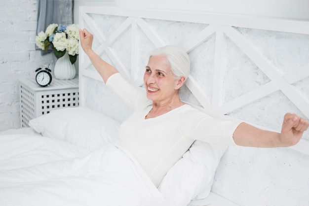Mujer mayor despertándose en la cama