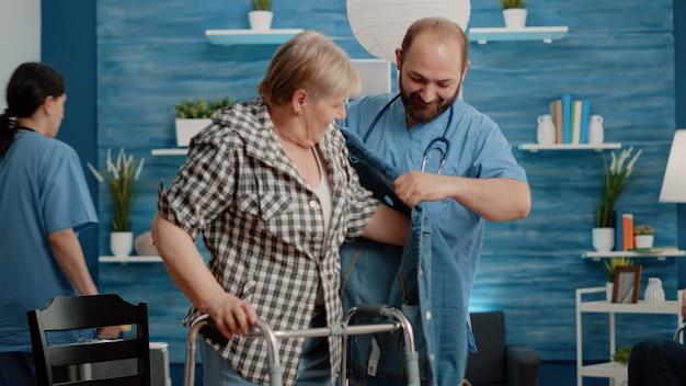 Mujer mayor con discapacidad recibiendo ayuda de enfermero
