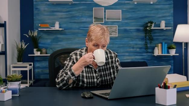 Mujer mayor disfrutando de una taza de café mientras trabaja en la computadora portátil en la sala de estar mientras su esposo está sentado en el sofá y leyendo un libro en segundo plano. señora mayor madura viendo formación empresarial en línea