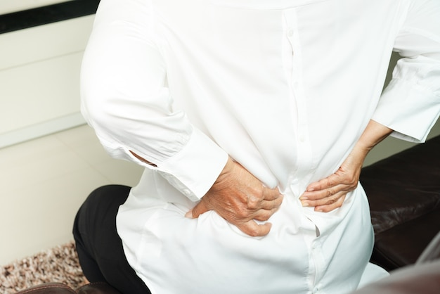 Mujer mayor dolor de espalda en casa, concepto de problema de salud