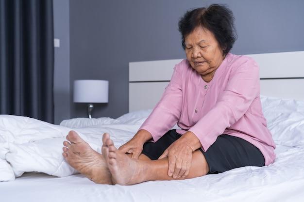 Mujer mayor con dolor en la pierna en la cama