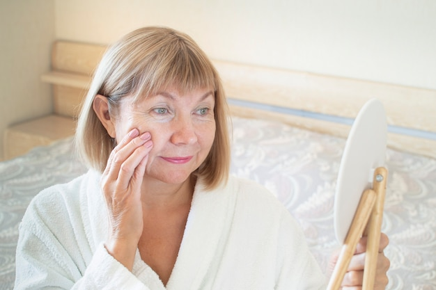 Mujer mayor en el dormitorio aplicando loción anti-envejecimiento. mira en un espejo cosmético. concepto anti edad, asistencia sanitaria y cosmetología, pensionista y maduro