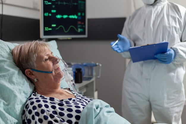 Mujer mayor enferma inhalar y exhalar a través de la máscara de oxígeno