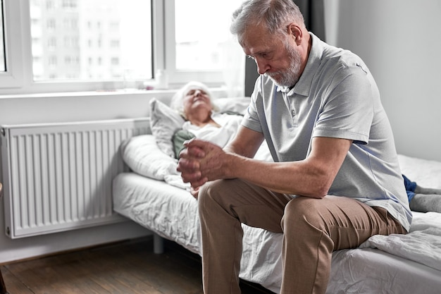 Mujer mayor enferma con su esposo anciano cariñoso sentado cerca de ella, apoyo y ayuda, el hombre se sienta con la cabeza hacia abajo. concepto de medicina
