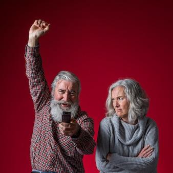 Una mujer mayor enojada con los brazos cruzados mirando a su esposo animando sosteniendo el control remoto en la mano