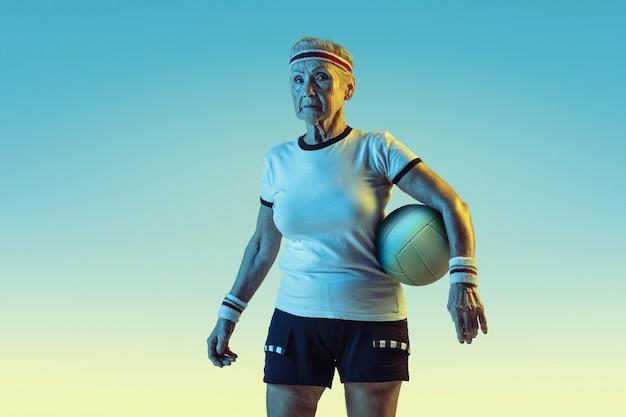 Mujer mayor en entrenamiento de ropa deportiva en voleibol sobre fondo degradado, luz de neón. modelo femenino en gran forma se mantiene activo. concepto de deporte, actividad, movimiento, bienestar, confianza. copyspace.