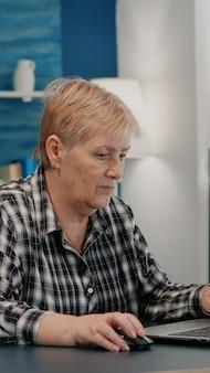 Mujer mayor con exceso de trabajo trabajando desde casa en el portátil