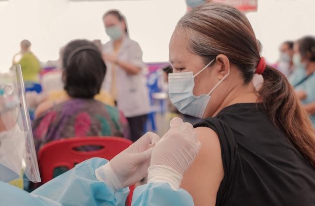 Mujer mayor de fat asia ha ido a vacunar el coronavirus covid con personal médico en un hospital de campo