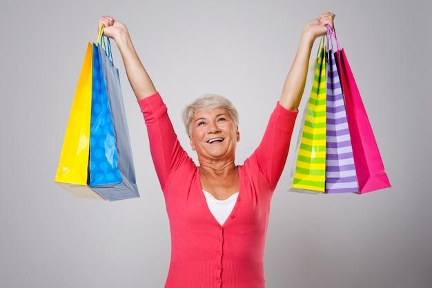 Mujer mayor feliz con bolsas de la compra.