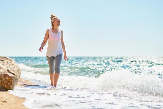 Mujer mayor feliz camina por el mar.