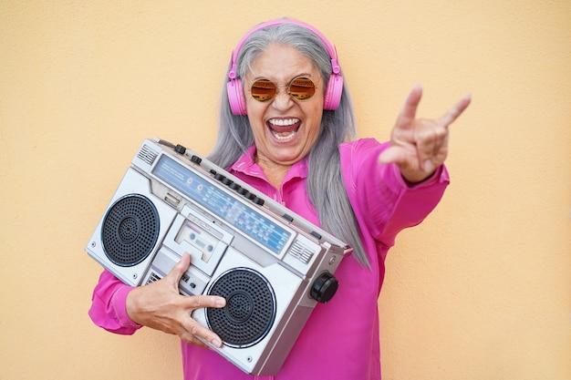 Mujer mayor feliz escuchando música rock con estéreo vintage boombox
