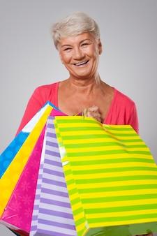 Mujer mayor feliz con lleno de bolsas de la compra.