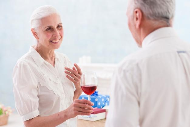 Mujer mayor feliz ofreciendo copa de vino a su marido