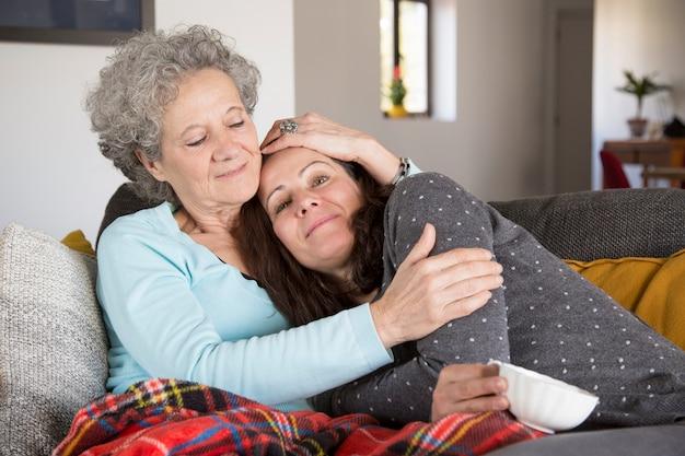 Mujer mayor feliz que abraza a la hija mientras que se sientan en el sofá