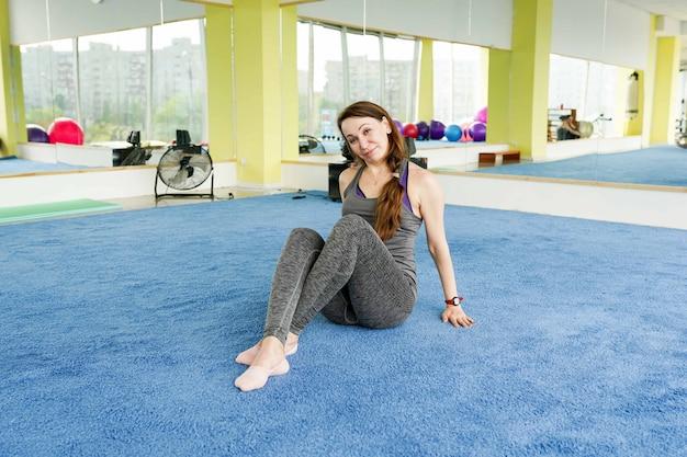 Mujer mayor feliz que descansa sobre la estera después de ejercicio en gimnasio
