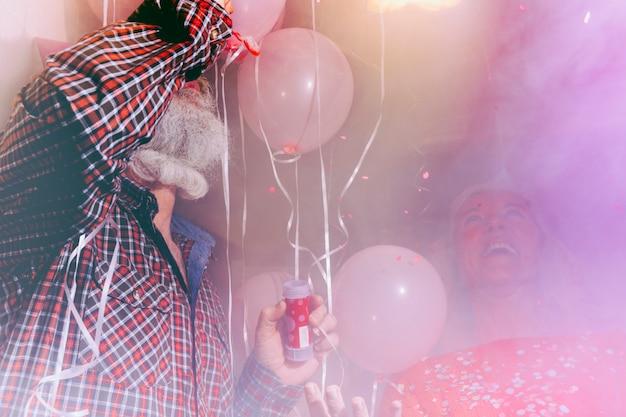 Mujer mayor feliz que mira a su marido que sopla la varita de la burbuja en el cuarto lleno de humo