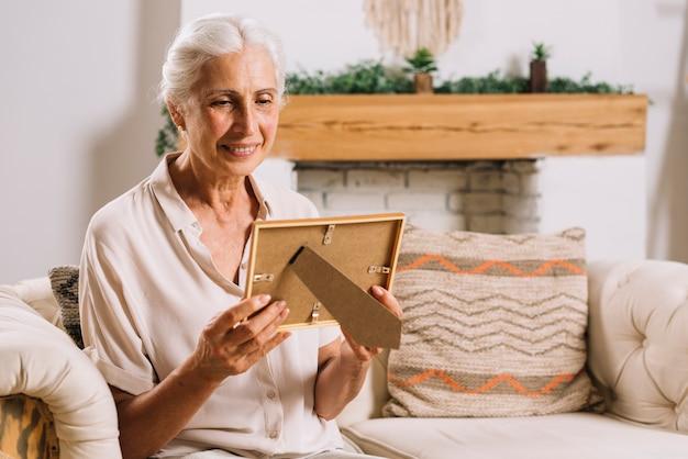 Mujer mayor feliz que se sienta en el sofá que mira el marco de la foto