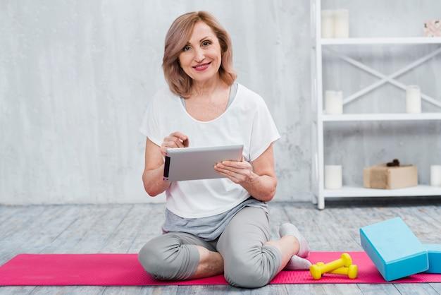 Mujer mayor feliz que usa el ordenador portátil cerca del equipo de la yoga