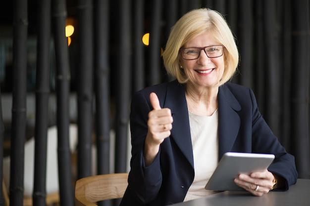 Mujer mayor feliz con la tableta en el café