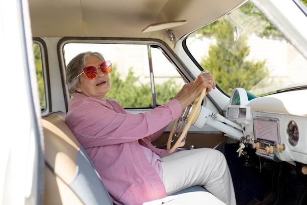 Mujer mayor feliz viajando sola en coche