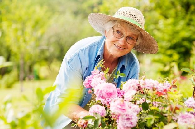 Mujer mayor, con, flores, en, jardín