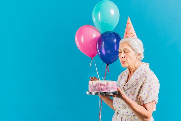 Mujer mayor con los globos y la vela que sopla de la torta de cumpleaños en fondo azul