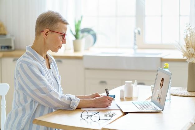Mujer mayor hablando en línea con el médico durante el covid mientras está sentado en la cocina de casa
