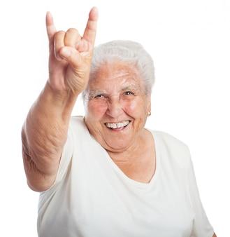 Mujer mayor haciendo cuernos con la mano