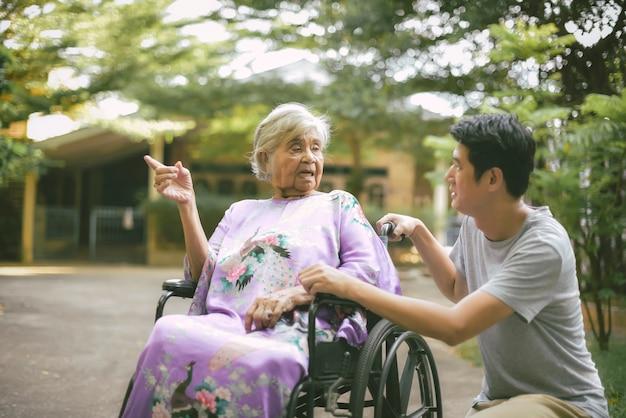 Mujer mayor con hija; enfermera cuidando a senior mujer en silla de ruedas