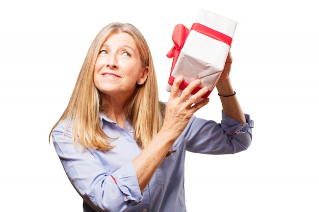 Mujer mayor intentando saber que tiene un regalo