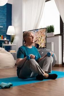 Mujer mayor jubilada sentada en la estera de yoga sosteniendo mancuernas de fitness en posición de loto durante la rutina de bienestar de pilates