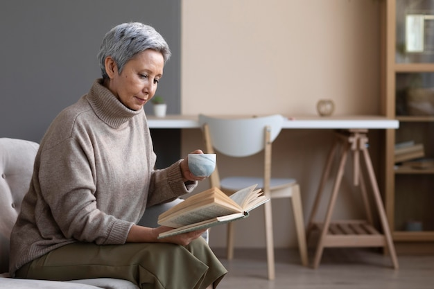 Mujer mayor leyendo un libro en casa