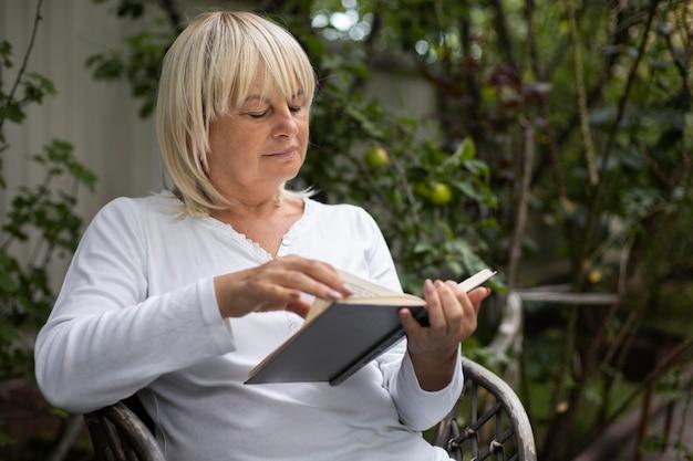 Mujer mayor leyendo un libro para su próxima clase