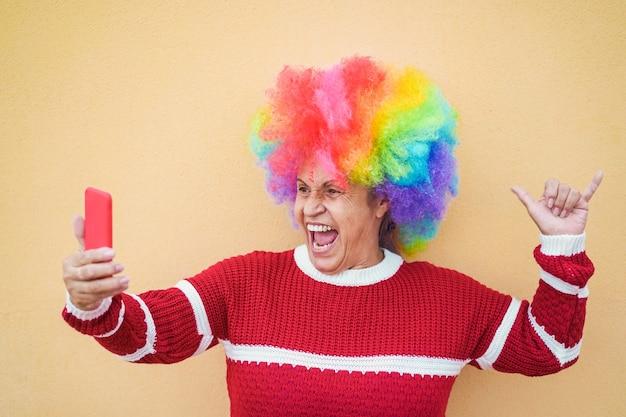Mujer mayor loca que usa el teléfono móvil mientras escucha la lista de reproducción de música rock